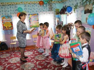 Воспитатель Татьяна Михайловна Вуколова вручает своим выпускникам подарки