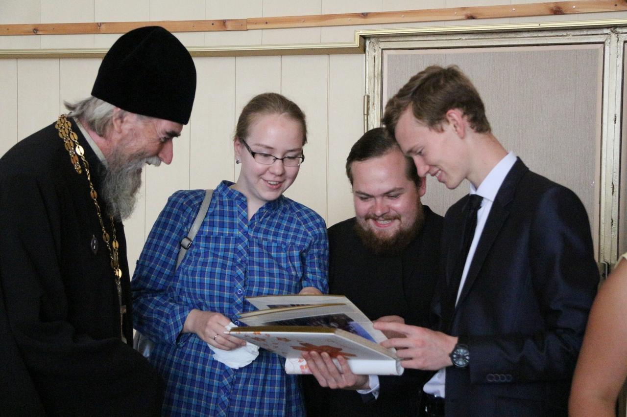 Отец Георгий и воспитанники с интересом рассматривали альбом с фотографиями, на которых запечатлены самые яркие события из жизни школы