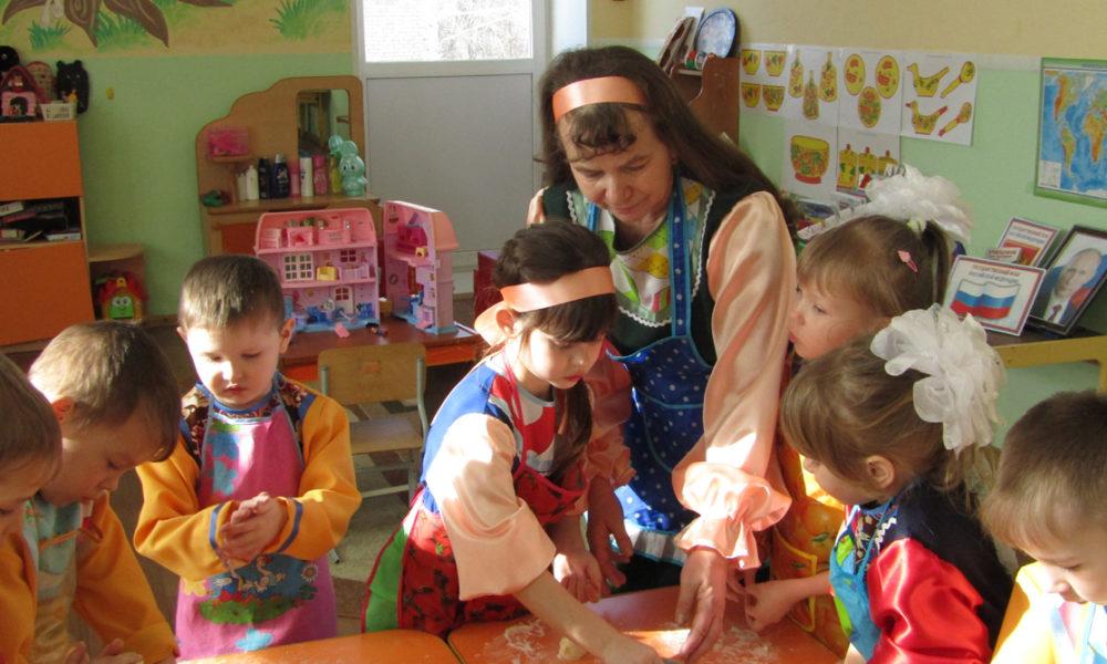 Людмила Васильевна вместе с детьми лепит куличики на праздник сороки