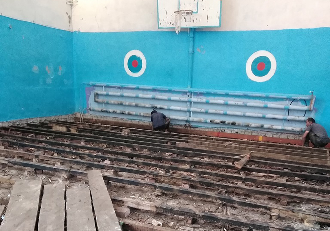 Рабочие демонтируют старый пол в школьном спортзале