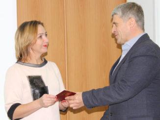 Галина Леонова получает значок и удостоверение из рук главы Игоря Колышева
