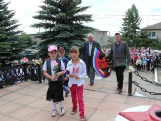 Иван Васильевич Гончаров и Малик Камильевич Сагдеев вместе с юными тюбукчанами возлагают венок и цветы к памятнику