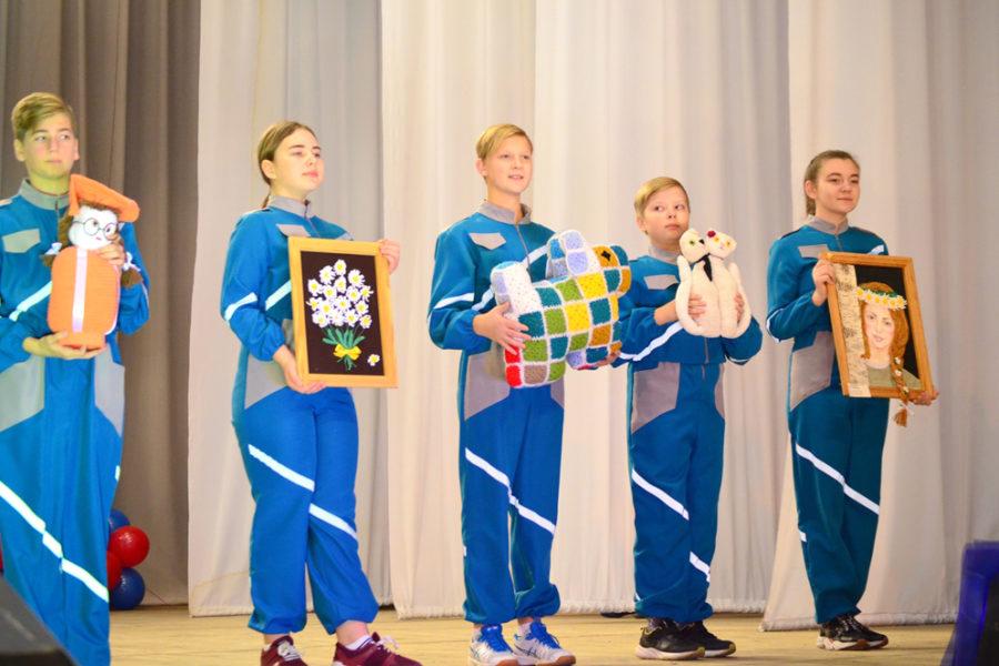 Участники коллектива «Мандарин» демонстрируют работы, выполненные воспитанниками кружка «Рукодельница»