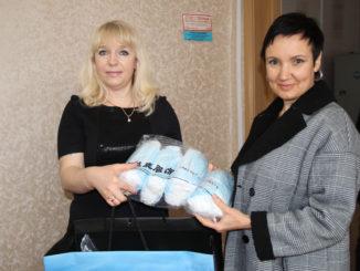 Елена Тарасова (справа) передает маски Татьяне Голуновой