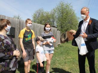 Депутат Законодательного Собрания области Олег Голиков вручает планшет семье Борисовых
