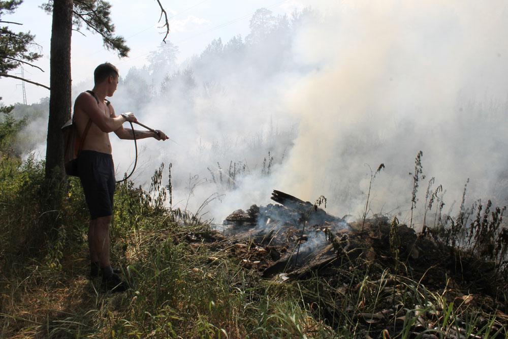 Доброволец Никита Возженин помогает пожарным тушить несанкционированную свалку на выезде из города Касли в сторону Кыштыма