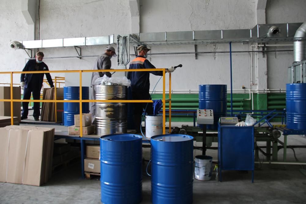 Рабочие занимаются покраской и упаковкой бочек