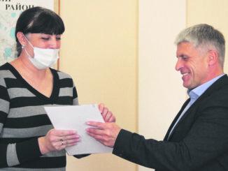 Ирина Кобелева, представитель ООО «Офисный мир», принимает поздравления и награду от главы района Игоря Колышева